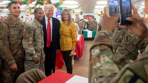 US President Donald Trump and First Lady Melania Trump take photos with members of the US military during an unannounced trip to Al Asad Air Base in Iraq on December 26, 2018. - President Donald Trump arrived in Iraq on his first visit to US troops deployed in a war zone since his election two years ago (Photo by SAUL LOEB / AFP)        (Photo credit should read SAUL LOEB/AFP/Getty Images)
