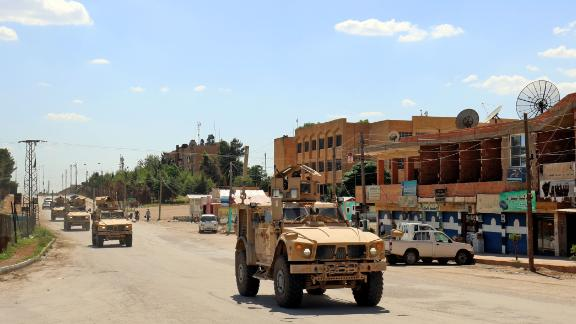 Vehicles of the US-led coalition battling the Islamic State group patrol the town of Rmelane in Syria