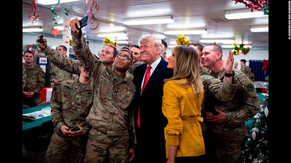 "President Donald Trump and first lady Melania Trump take a photo with military personnel in a dining hall at the Al Asad Air Base in Iraq, Wednesday, December 26. The <a href=""https://www.cnn.com/2018/12/26/politics/donald-trump-iraq-visit/index.html"" target=""_blank"">surprise trip</a> was Trump's first visit to troops stationed abroad in a combat zone."