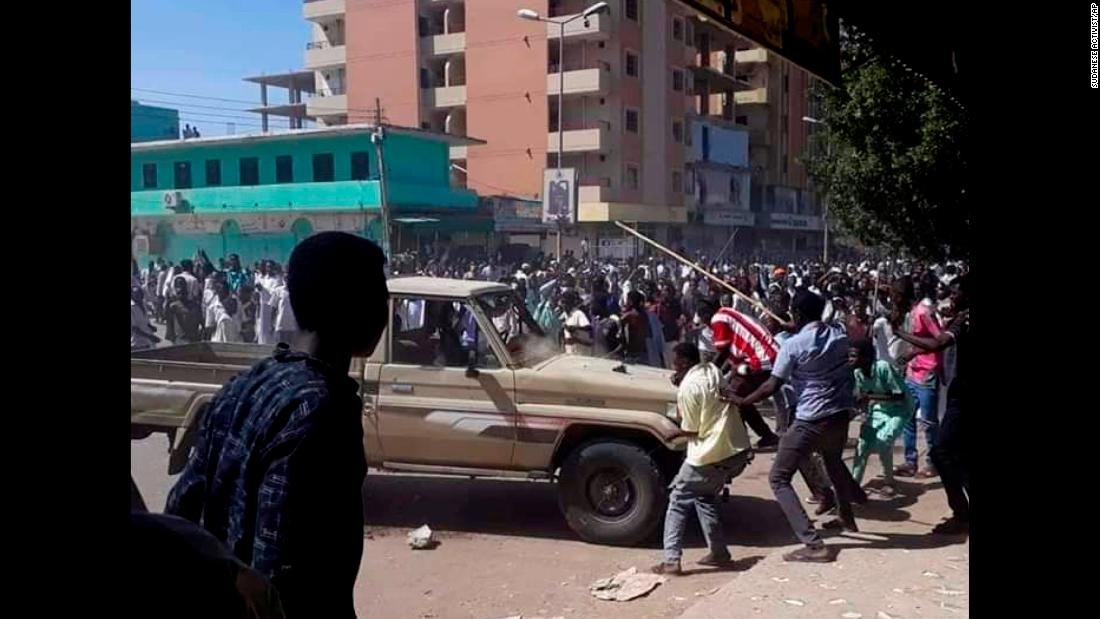 "In this Sunday, December 23 handout photo provided by a Sudanese activist, people chant slogans and attack a national security vehicle <a href=""https://www.cnn.com/2018/12/26/opinions/sudan-protests-press-freedoms-intl/index.html"" target=""_blank"">during a protest</a>, in Kordofan, Sudan."