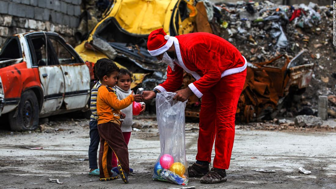 An man dressed in a Father Christmas suit distributes gifts to children in the old city of Mosul, Iraq, on Wednesday, December 26.