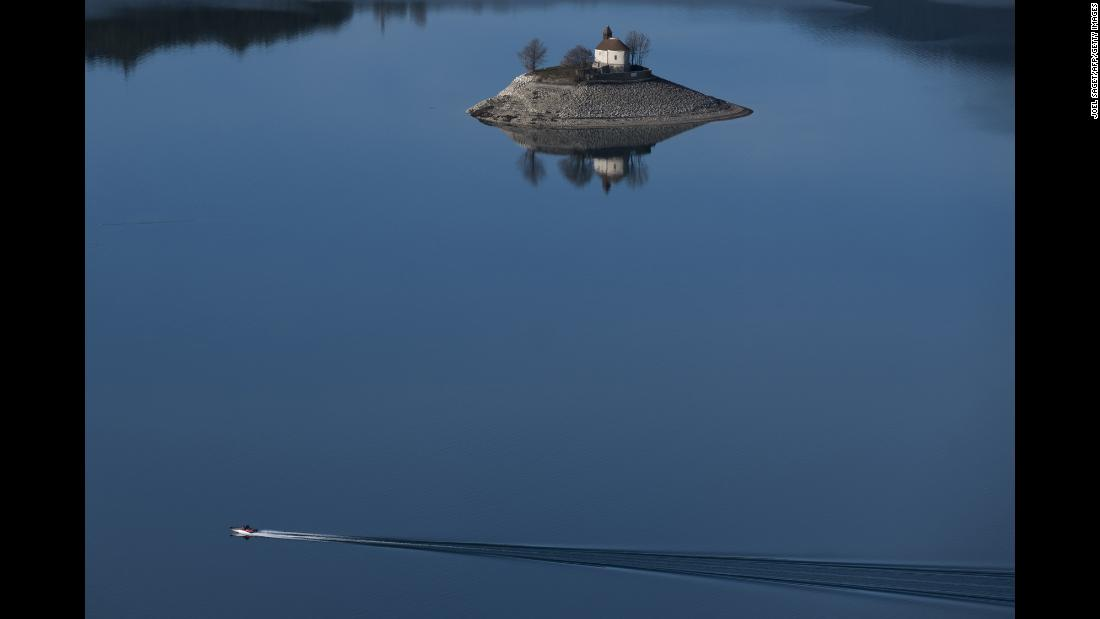 A boat passes by the Saint-Michel Chapel on Serre-Ponçon lake in Savines-le-Lac, France, on December 26.