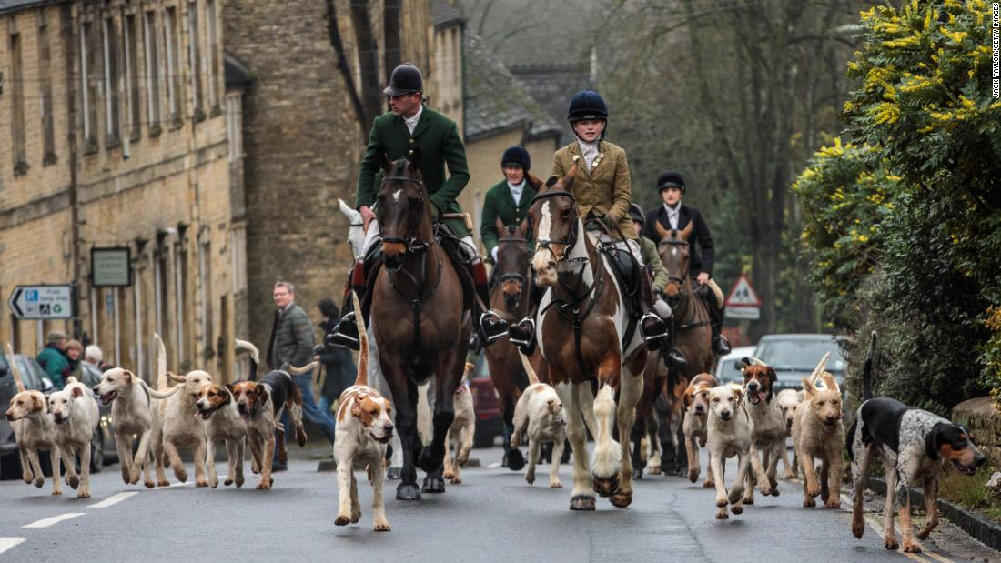 Riders of the Heythrop Hunt and their hounds arrive in the Chipping Norton town center on Boxing Day, December 26, in Oxfordshire, England.
