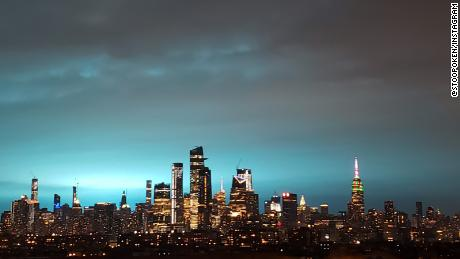 The blue glow spread across the city's many skyscrapers.
