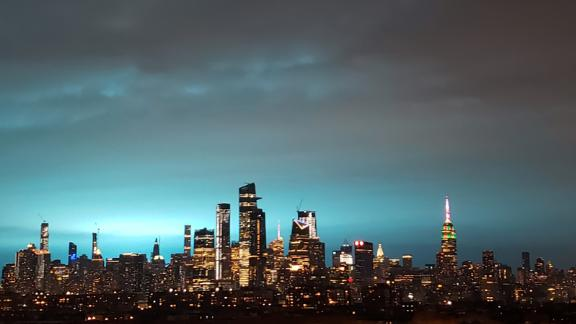 New York's skyscrapers shimmer in a blue glow Thursday night.