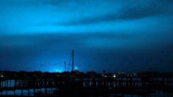 NEW YORK, USA - DECEMBER 27: Birds fly over a pier as a blue light illuminates the night sky after a transformer explosion at Queens Borough in New York, United States on December 27, 2018. (Photo by Simin Liu/Anadolu Agency/Getty Images)