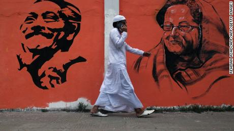 A man walks past a wall with images of Bangladeshi founding father Sheikh Mujibur Rahman and Prime Minister Sheikh Hasina Wazed in Dhaka, Bangladesh.