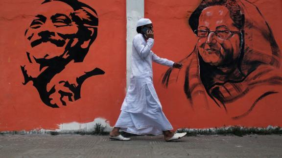 A man walks past a wall with images of Bangladeshi founding father Sheikh Mujibur Rahman and Prime Minister Sheikh Hasina Wazed in Dhaka, Bangladesh.