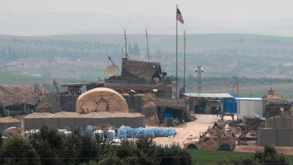 US forces' vehicles and structures are seen on the outskirts of the northern Syrian town of Manbij in the village of Dadat, on the demarcation line separating pro-Turkish factions and opposing US-backed Syrian Kurdish fighters, on December 26, 2018. - Pro-Turkish armed groups have reinforced their presence on the outskirts of the city of Manbij in northern Syria as Ankara threatens a new offensive against Kurdish forces. The United States has backed Kurdish fighters in northern Syria as part of an international coalition against the Islamic State jihadist group. But a surprise announcement by US President Donald Trump a week ago that he will pull American troops out of the country has left the Kurds exposed to attack. (Photo by Delil souleiman / AFP)        (Photo credit should read DELIL SOULEIMAN/AFP/Getty Images)