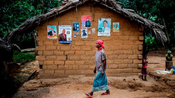 A woman walks in front of electoral posters in the remote village of Bonde, Kongo Central province, on December 26.