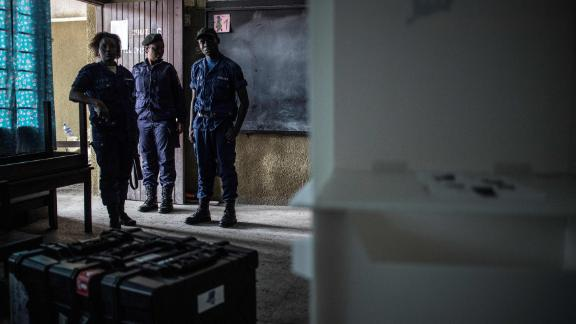 Congolese policemen guard voting machines in a school where the voting material is stocked in Kinshasa's Victoire district.
