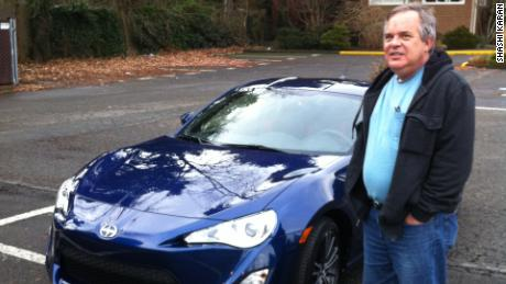 Alan Naiman poses next to one of his few splurges -- a Scion sports car. The thrifty social worker left more than $11 million to charities when he died in January.