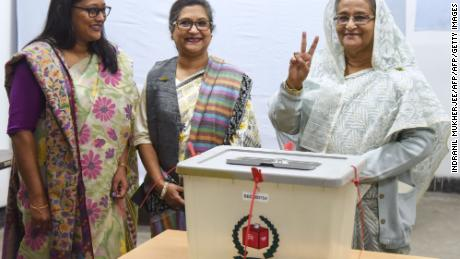 Bangladeshi Prime Minister Sheikh Hasina (right) shows the symbol of victory after casting her vote.