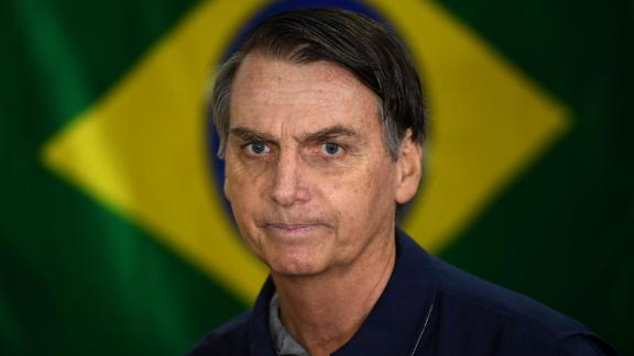TOPSHOT - Brazil's right-wing presidential candidate for the Social Liberal Party (PSL) Jair Bolsonaro walks in front of the Brazilian flag as he prepares to cast his vote during the general elections, in Rio de Janeiro, Brazil, on October 7, 2018. - Polling stations opened in Brazil on Sunday for the most divisive presidential election in the country in years, with far-right lawmaker Jair Bolsonaro the clear favorite in the first round. About 147 million voters are eligible to cast ballots and choose who will rule the world's eighth biggest economy. New federal and state legislatures will also be elected. (Photo by Mauro PIMENTEL / AFP)