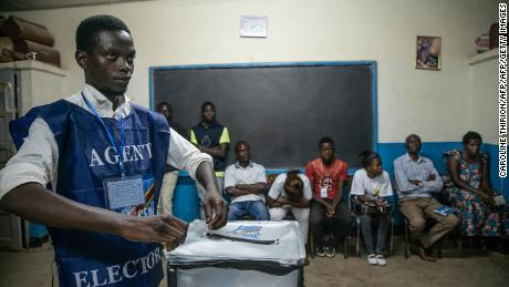 An electoral agent seals a ballot box in front of observers in Lubumbashi on December 30.