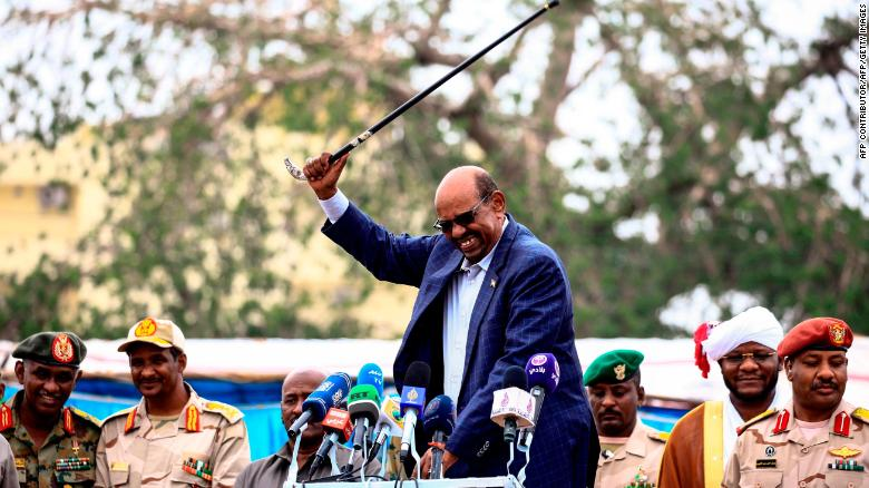 Omar al-Bashir waves his cane while giving a speech in Nyala, the capital of South Darfur province, on September 21, 2017.