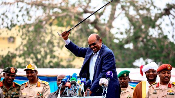 Sudanese President Omar al-Bashir (C) waves a walking stick as he gives a speech in Nyala, the capital of South Darfur province, on September 21, 2017. Bashir, wanted by the International Criminal Court on charges of genocide and war crimes related to the conflict in Darfur, is touring the region ahead of a US decision to be made on October 12, 2017 on whether to permanently lift a decades-old trade embargo on Sudan. / AFP PHOTO / ASHRAF SHAZLY        (Photo credit should read ASHRAF SHAZLY/AFP/Getty Images)