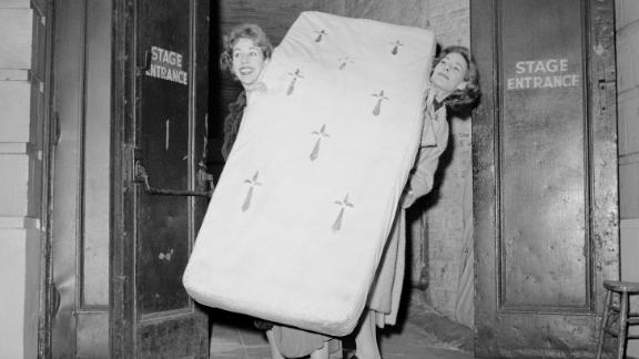 """Burnett, left, and Mary Rodgers move a prop mattress through the stage door of the Alvin Theatre in New York in 1959. Burnett's first Broadway play was the musical """"Once Upon a Mattress,"""" and Rodgers wrote the score. Burnett earned a Tony Award nomination for her work on the play."""