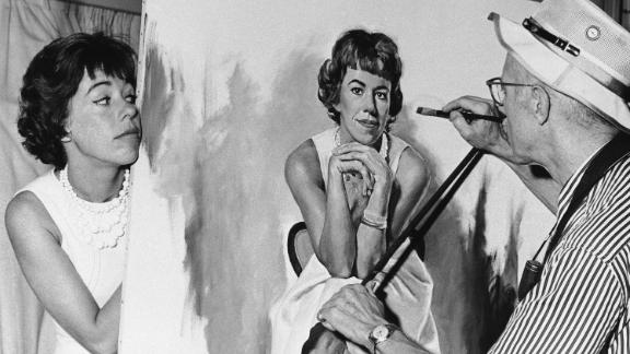 Burnett peeks at a portrait of herself that was being painted by artist Dmitri Vails in 1963.