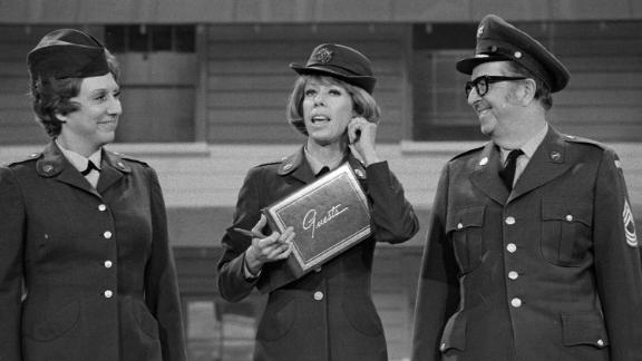 """Burnett — flanked by Jean Stapleton and Phil Silvers — tugs on her ear during an episode of """"The Carol Burnett Show"""" in 1975. Burnett's signature ear tug came at the end of each episode and was her way of saying hello to her grandmother who raised her."""