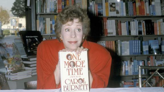 """Burnett poses with her memoir """"One More Time"""" at a book signing in Beverly Hills, California, in 1986."""