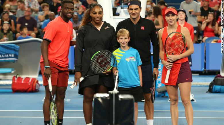 Serena Williams (second left) and Roger Federer are flanked by teammates Frances Tiafoe and Belinda Bencic as they line up before the start of their mixed doubles clash at the Hopman Cup.