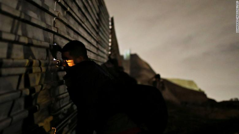 A man looks through the fence as he and others prepare to cross it illegally on Monday.