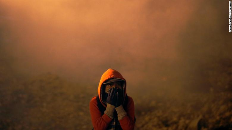 A migrant, part of a caravan of thousands from Central America trying to reach the United States, covers his face after U.S. Customs and Border Protection (CBP) throw tear gas to the Mexican side of the fence as they prepared to cross it illegally, in Tijuana, Mexico, January 1, 2019. REUTERS/Mohammed Salem