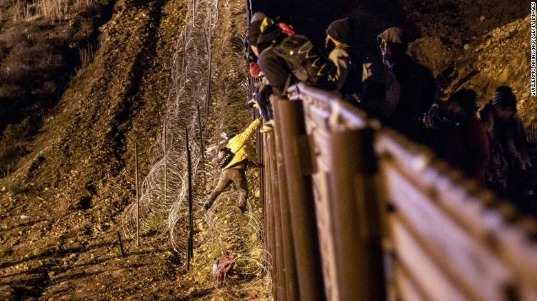 A migrant is lowered toward concertina wire on the US side of the border fence.