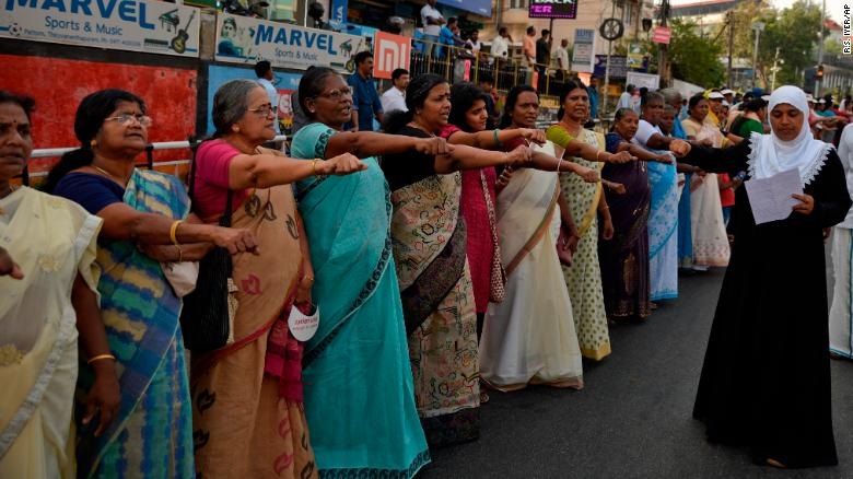 "Women raise their hands to take a pledge to fight gender discrimination as they form part of a hundreds kilometer long ""women's wall."""