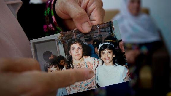 Fadwa Tlaib, an aunt of Rashida Tlaib points to a young Rashida in a 1987 picture with her mother, Fatima, and brother, Nader, at the family house in the West Bank village of Beit Ur al-Foqa on August 8, 2018.