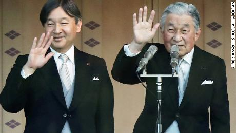 Japan's Emperor Akihito (R) and Crown Prince Naruhito (L) wave to the crowd during the New Year's greeting ceremony at the Imperial Palace in Tokyo on January 2, 2019.