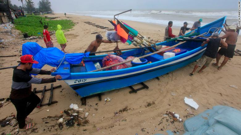 Thai men move a fishing boat to a safer location in Songkhla, southern Thailand, in preparation for storm weather conditions on Thursday.
