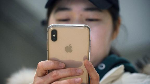 A woman uses an Apple iPhone at a shopping mall in Beijing on January 3, 2019.