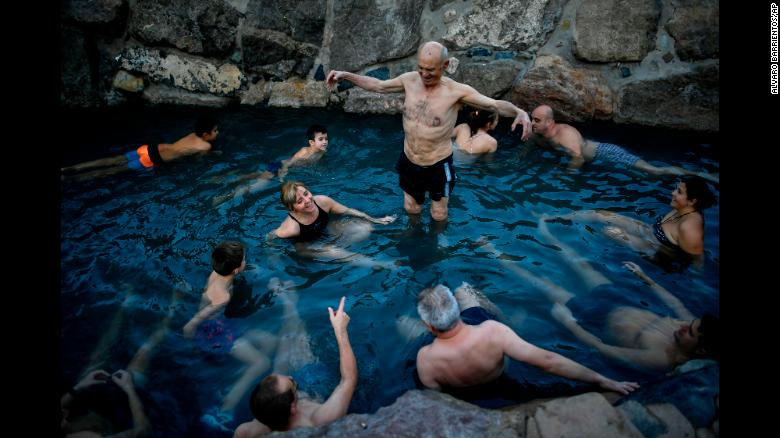 Jose Antonio Aznarez, center, stands in a natural thermal bath during a cold winter morning in Arnedillo, Spain, on Saturday, December 29.