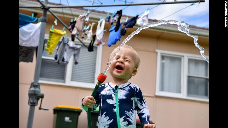 Harry Mayer plays with a garden hose on a hot day in Liverpool, Australia, on Sunday, December 30.