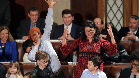 Rashida Tlaib wears a traditional Palestinian gown, as her son does a dance move, the dab.
