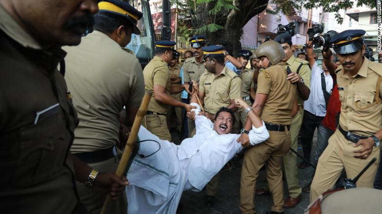 Police carry away a protester in Kochi, Kerala, after two women successfully entered a shrine they were previously barred from visiting.
