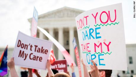 Affordable Care Act supporters hold up signs outside the Supreme Court as they wait for the court's decision on Obamacare on Thursday, June 25, 2015. (Photo By Bill Clark/CQ Roll Call via AP Images)
