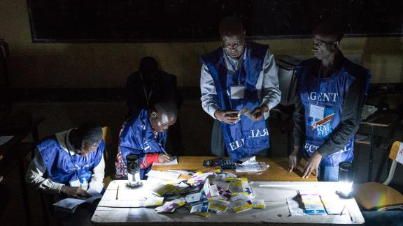 Electoral commission agents count votes during an electricity cut while watched by observers at Kiwele college in Lubumbashi on December 30, 2018.