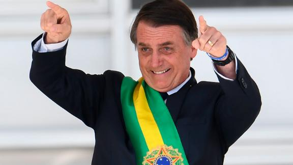 Brazil's new president Jair Bolsonaro gestures after receiving the presidential sash from outgoing Brazilian president Michel Temer (out of frame), at Planalto Palace in Brasilia on January 1, 2019.