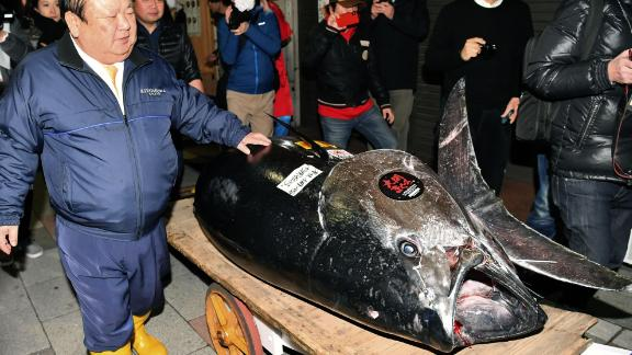 """Kiyoshi Kimura, the """"Tuna King,"""" stands with the bluefin tuna that reached a record price at the 2019 New Year's auction."""