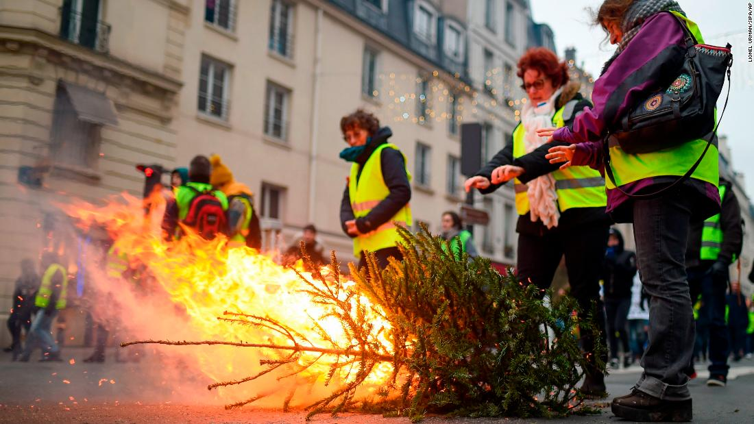 Protesters warm their hands over a burning tree in a Paris street on January 5.