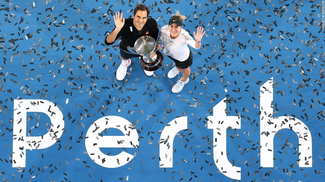 Swiss tennis players Roger Federer and Belinda Bencic pose with the Hopman Cup after winning the team tournament in Perth, Australia, on Saturday, January 5.
