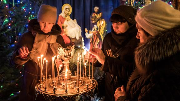 "KIEV, UKRAINE - JANUARY 06: Worshippers ight candles during Christmas services at St. Michael's Golden-Domed Monastery, the main church of the new Orthodox Church of Ukraine, on January 6, 2019 in Kiev, Ukraine. The independent Orthodox Church of Ukraine, which previously fell under the authority of Moscow, was granted official recognition today in a decree, or ""tomos,"" signed by the Ecumenical Patriarch of Constantinople in a move with deep historical roots but fueled by contemporary political conflict between Ukraine and Russia. (Photo by Brendan Hoffman/Getty Images)"