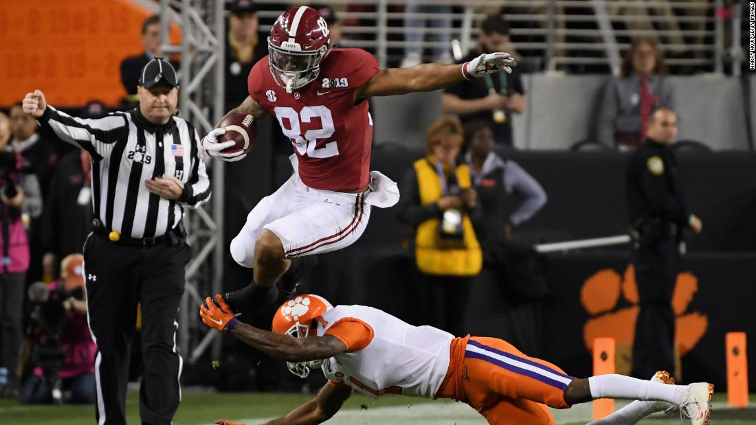 Alabama's Irv Smith Jr. leaps over a tackle from Trayvon Mullen in the first quarter.