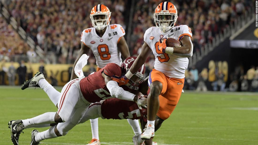 Etienne eludes Alabama defenders on his way to a 17-yard touchdown run in the first quarter. The Tigers led 14-7 after the extra point.
