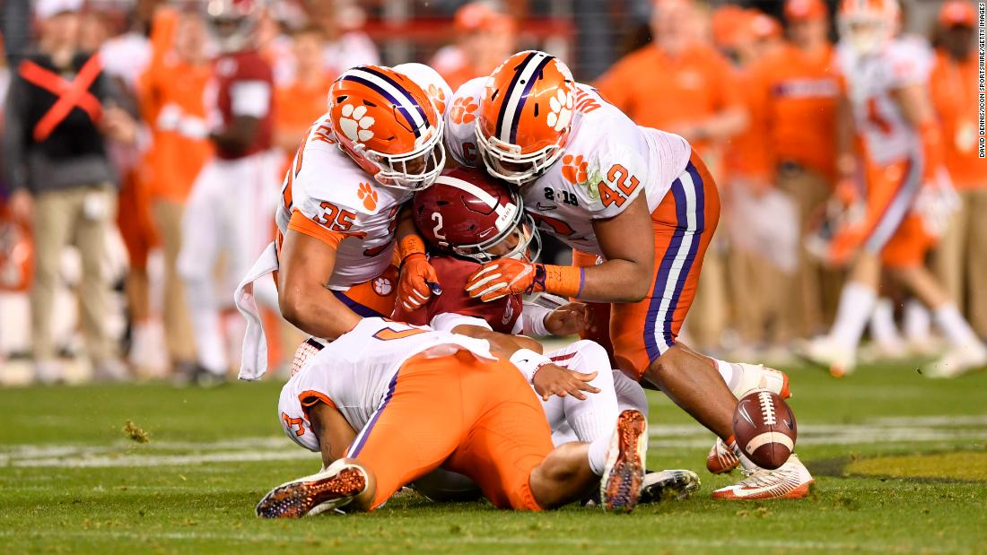 Clemson defenders swarm Alabama quarterback Jalen Hurts late in the game.