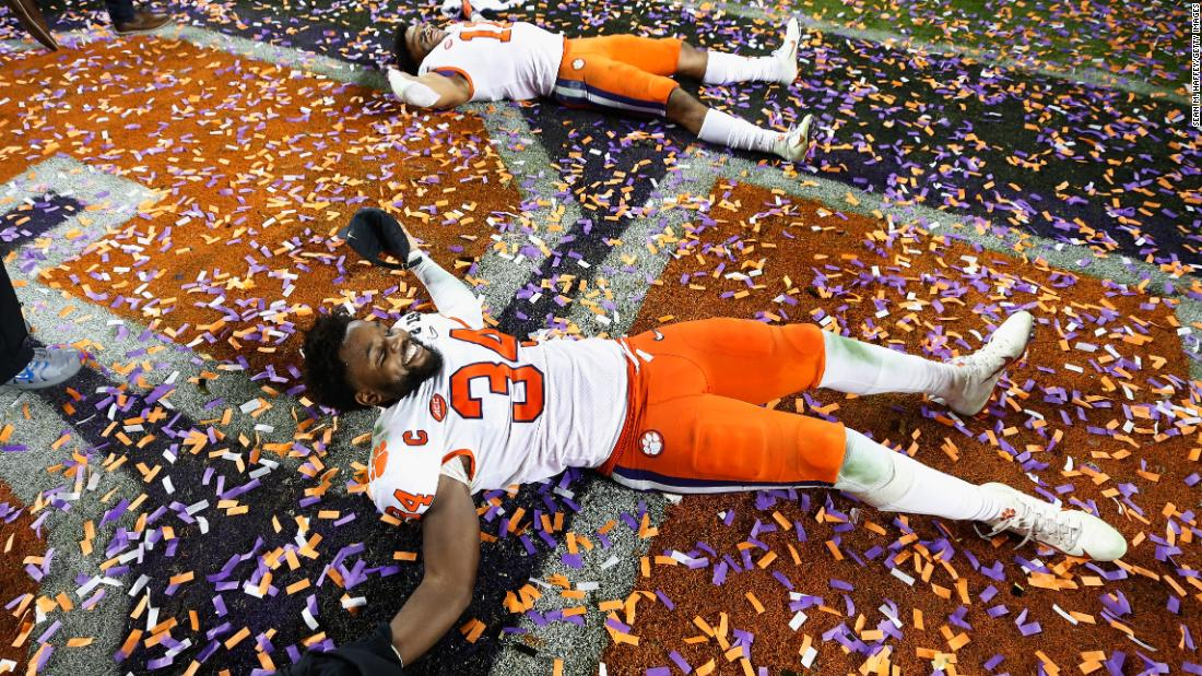 Clemson players make confetti angels on the field.