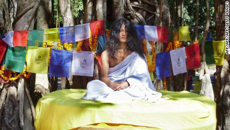 Ram Bahadur Bomjan sits on a platform before preaching to an audience in Bara district, 62 miles south of Kathmandu, in this file photograph from November 10, 2008.